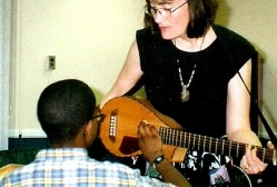 Margo Hennebach demonstrates her instrument to Dwayne in a shelter program